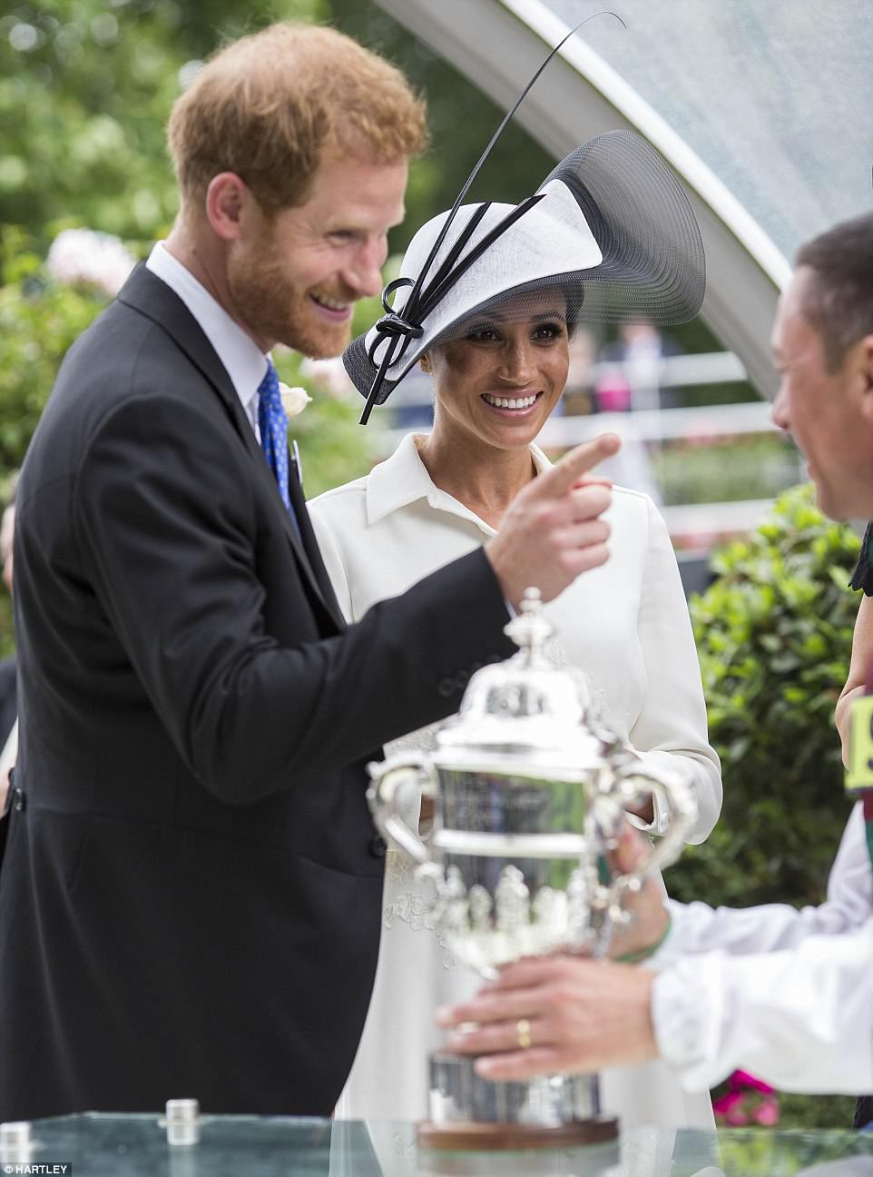 Prince Harry was snapped playfully wagging a finger at the jockey, who said Meghan 'giggled' when he told her his son would be pleased to know she had presented his trophy