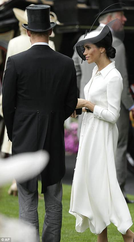 The Duchess of Sussex looked elegant in a white Givenchy dress and black and white fascinator as she joined Prince Harry at Ascot today