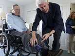 """Former Democratic President Bill Clinton jokes with former Republican President George H.W. Bush as Bush shows off a pair of """"Bill Clinton socks,"""" while Clinton visits Bush at his home in Kennebunkport, Maine, Monday, June 25, 2018. (Evan F. Sisley/Office of George Bush via AP)"""