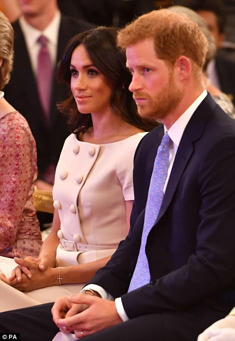 Think pink! Meghan wore a powder pink dress featuring oversized buttons and teamed with a pair of sensible black courts