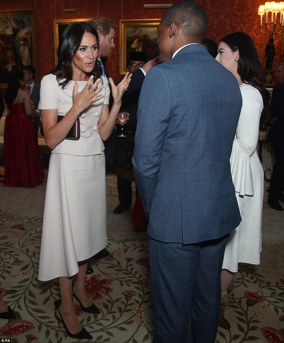 In her element: A sharply-dressed Meghan was all smiles and looked in her element as she spoke to guests