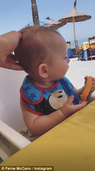Doting parent: Another clip saw Ferne dote on Sunday as they ate food by the beach, as her little one seemed to really be enjoying her mango slice