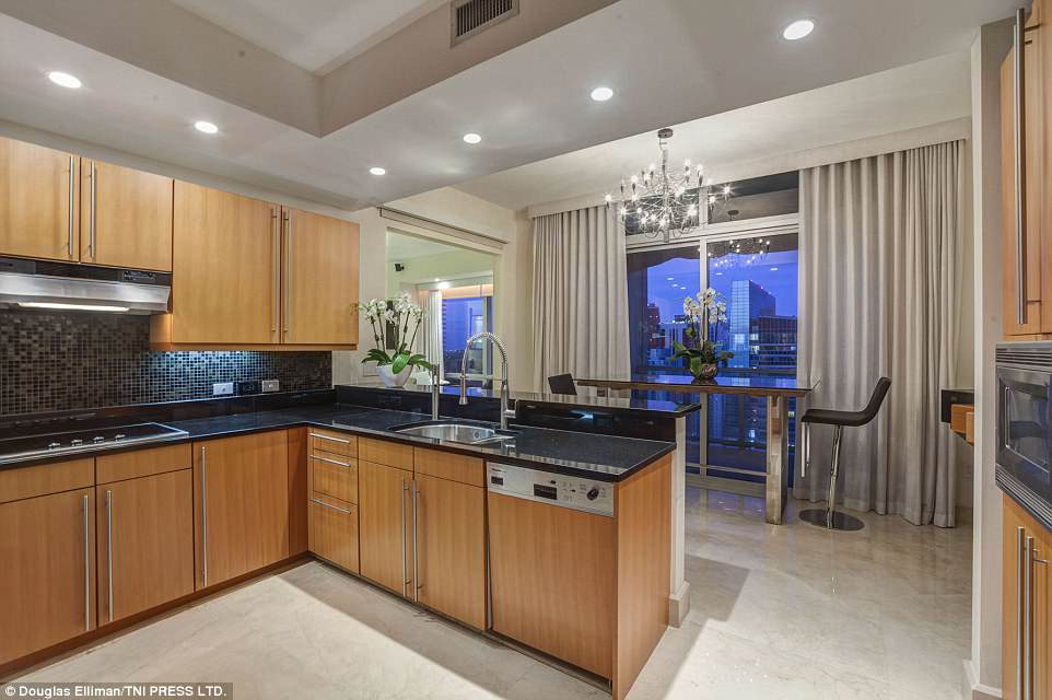 Whip something up: The kitchen is designed around a classic wood look with marble tabletops, and even includes a breakfast bar
