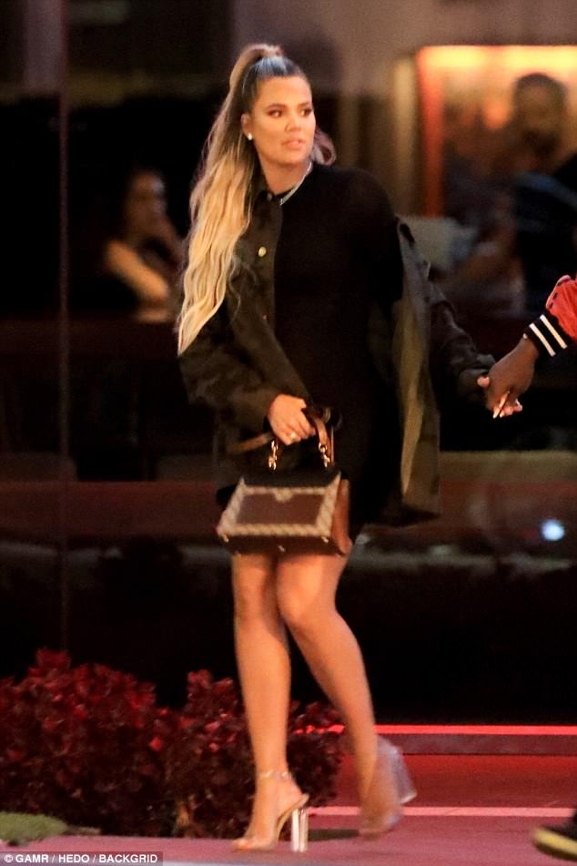 Bombshell: Khloe looked glam as she flashed her legs in a black outfit during her outing to BOA steakhouse with Tristan and pals on Sunday