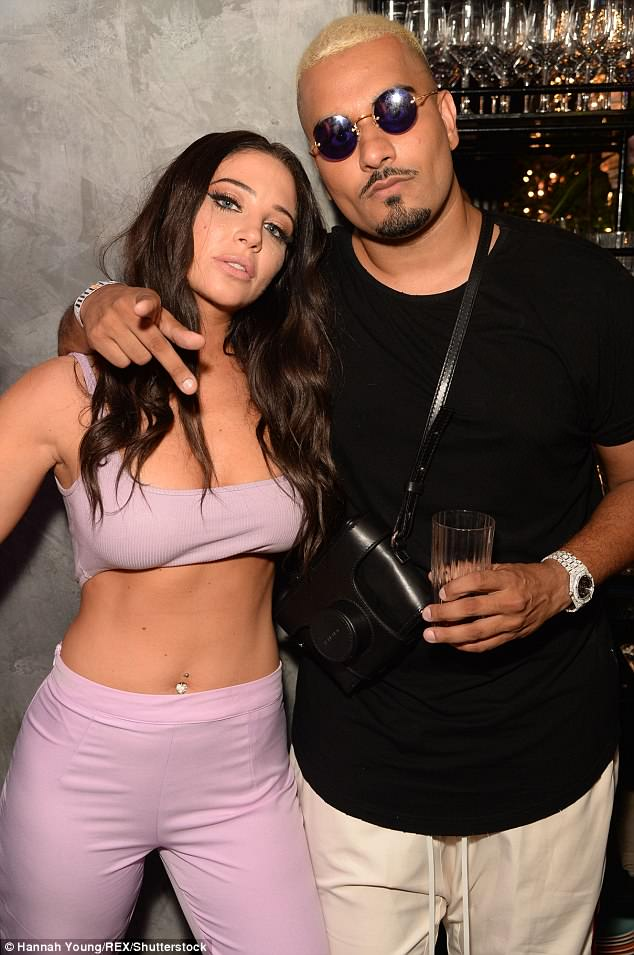 Strike a pose: Tulisa, 29, dressed to impress for the celeb-packed party in her tiny crop top as she posed up a storm with the clothing giant's billionaire founder Umar Kamani