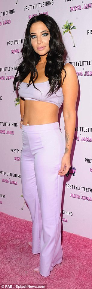 Coordinated: She teamed the minuscule top with a pair of high-waisted flared trousers in a matching shade of purple