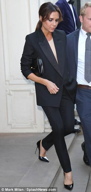 Let's go: Bodyguards ushered Victoria onto the street as she made an exit from the Dover Street store following her latest visit