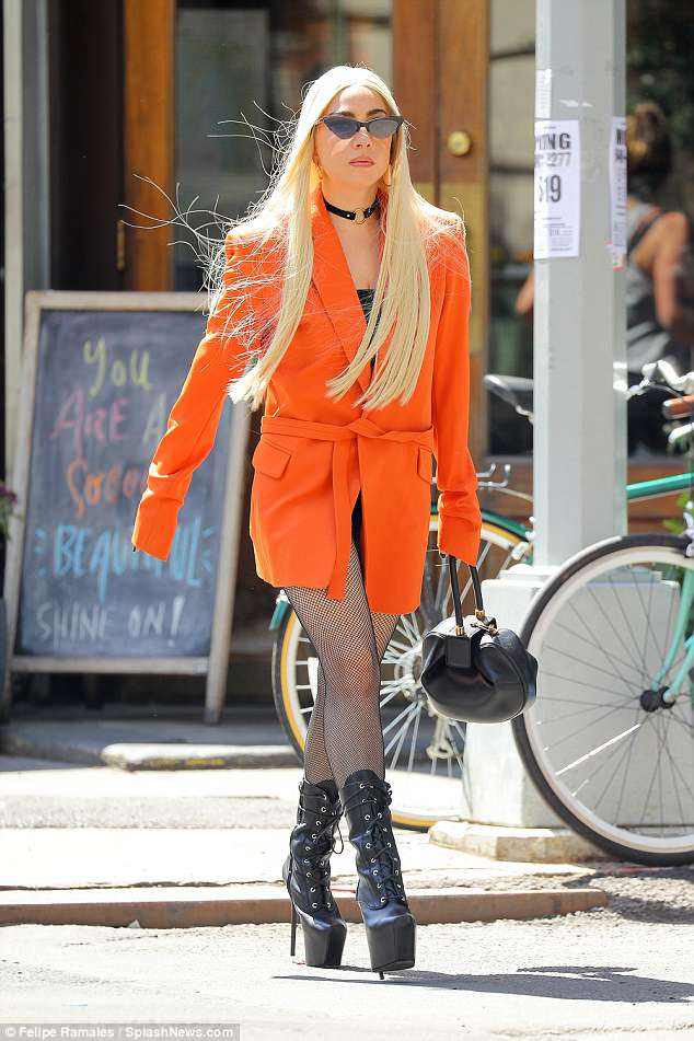 Eminently chic:She slid into a black top and clasped on a black choker, adding a blaze of color to the look with a bright orange jacket tied round her waist with a sash