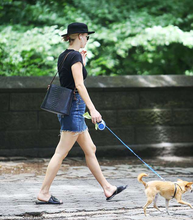 Solo in the city:The Hunger Games vet looked city chic as she paired a black T-shirt with a denim miniskirt that was frayed at the bottom and black slides