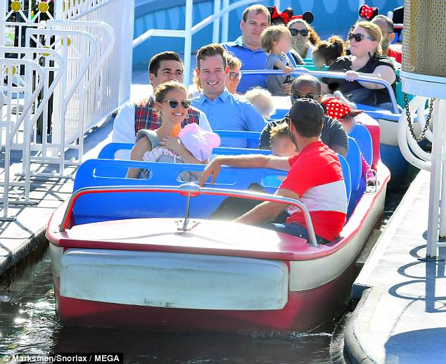 Leisurely cruise: The family also rode a water ride together with Benjamin, 41, sat in the front