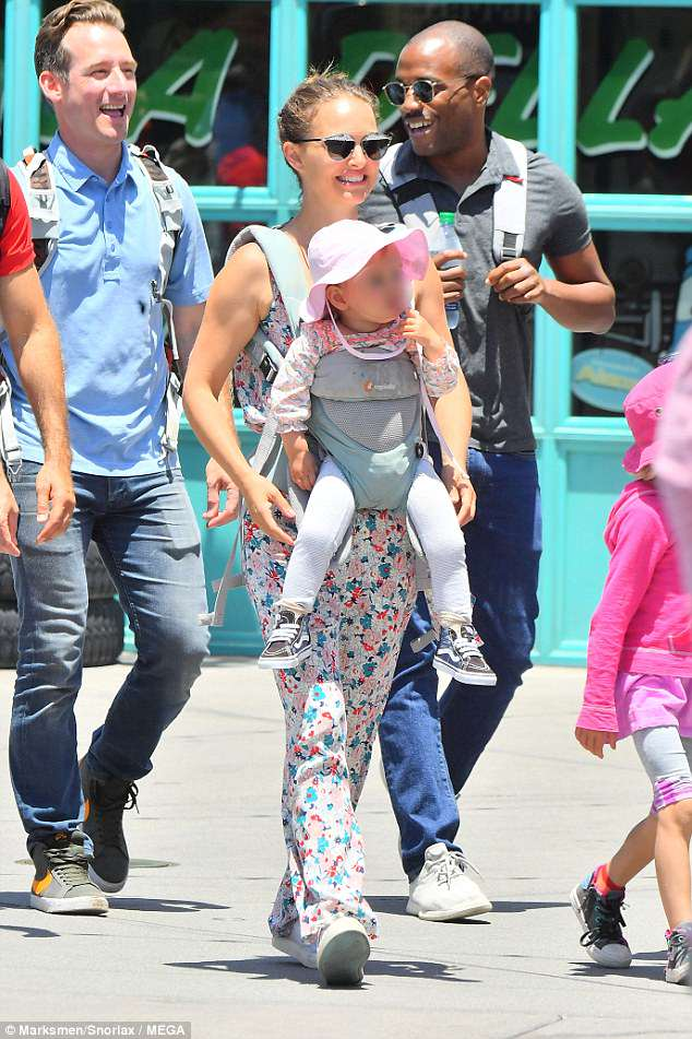 Adorable: Little Amalia wore a floral blouse to match mom and a floppy pink sun hat
