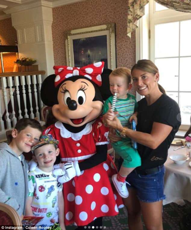 So cute!In another photo, Coleen - clad in a casual black T-shirt and denim cut-offs - cradled young son Kit in her arms next to Minnie Mouse