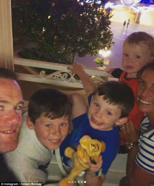 Making memories:In one particularly adorable snap, both Coleen and Wayne cuddled up to their boys as they overlooked the park from their hotel room