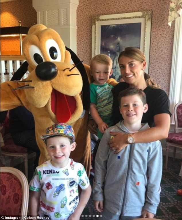 Smiles: The young boys made sure to pose with a bevy of characters while at the park, including Goofy (above), Eeyore and Tigger