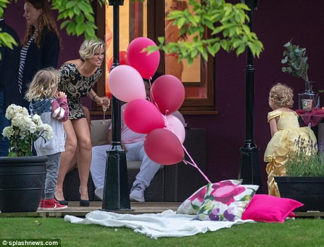 Doting mother: With five kids of her own, Kerry was also sure to play with Katie's youngest in the garden - with a glass of champagne in hand