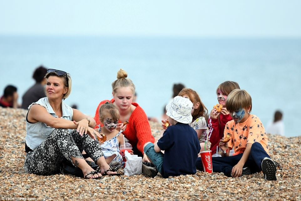 Lunch time! The singer reclined on the pebbles of the beach with her children as they tucked into some food