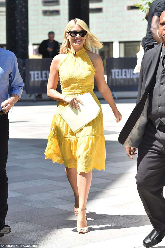 Sunny side up: Holly Willoughby, 37, looked sensational in a glorious yellow halterneck dress as she filmed in the sunshine for This Morning in London on Monday