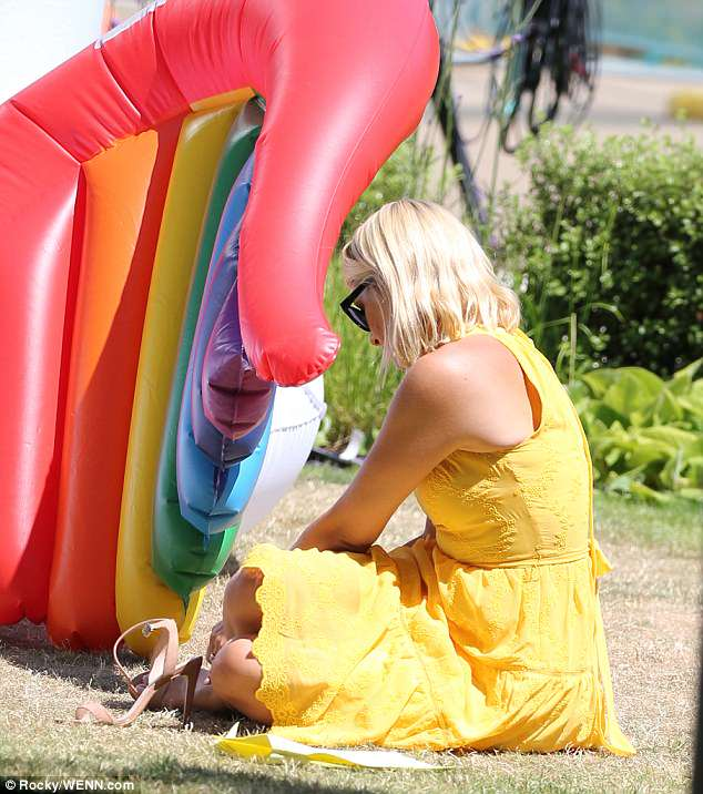 Having fun: She didn't let her skyscraper heels get in the way of filming on the gigantic inflatable rainbow unicorn, and stripped off her footwear to clamber into the massive float