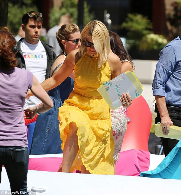 Larking about: The presenter concentrated on her footing as she clambered onto the brightly coloured unicorn float
