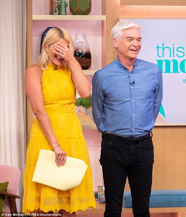 Getting the giggles: Holly could barely keep herself under control, as she was seen tittering next to Phil, while he tried to complete his intro
