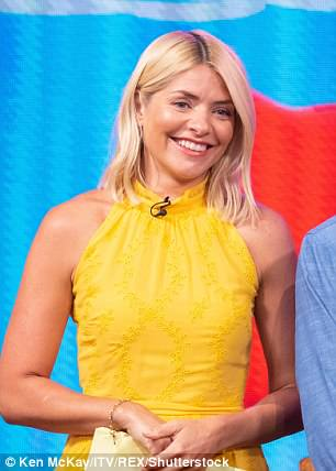 Holding it together: Holly was seen stifling giggles as she tried to carry on regardless