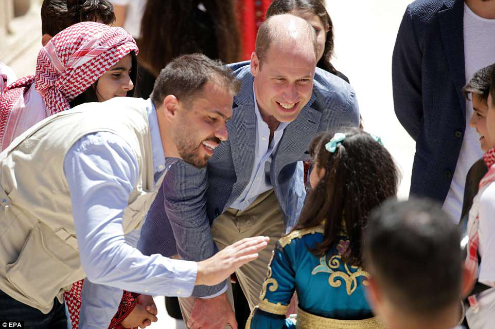 Prince William, Duke of Cambridge, talks to some of the children that showed off their art and performed for the visitors