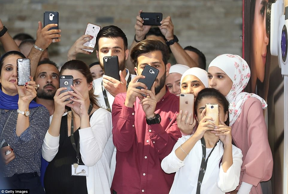 Students and wellwishers take photos as Prince William, Duke of Cambridge visits vocational training college Al Quds
