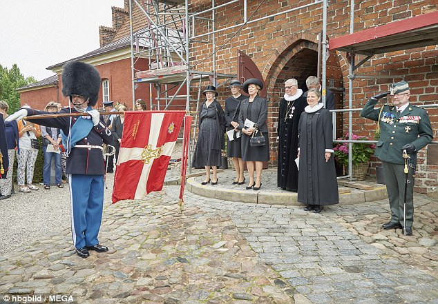 The mourners and well-wishers gathered to watch a flag waving service outside the church