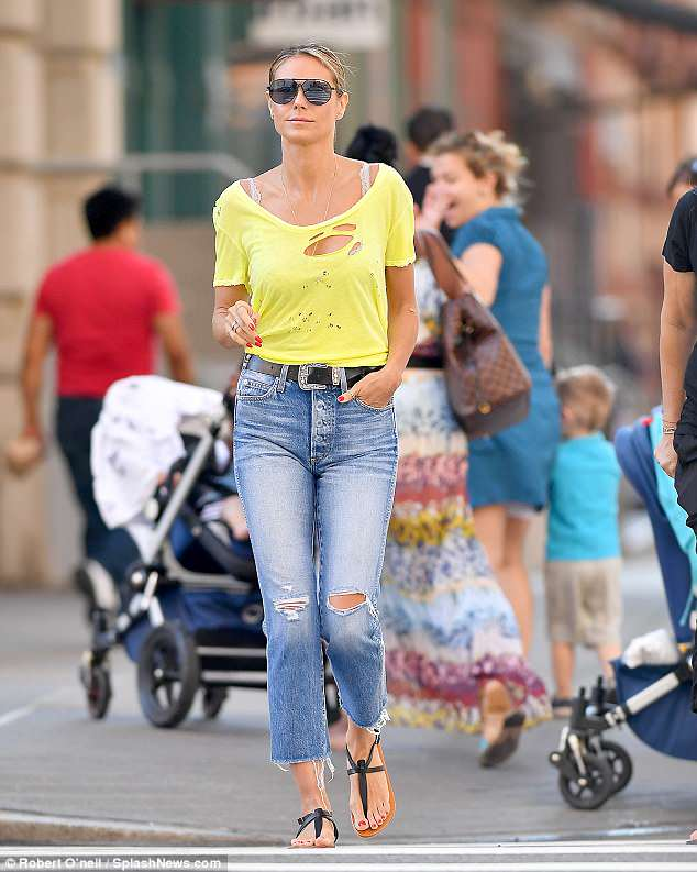 Lovely in lemon: Heidi Klum looked lovely in a yellow top and jeans as she made NYC into her stunning runway on Monday