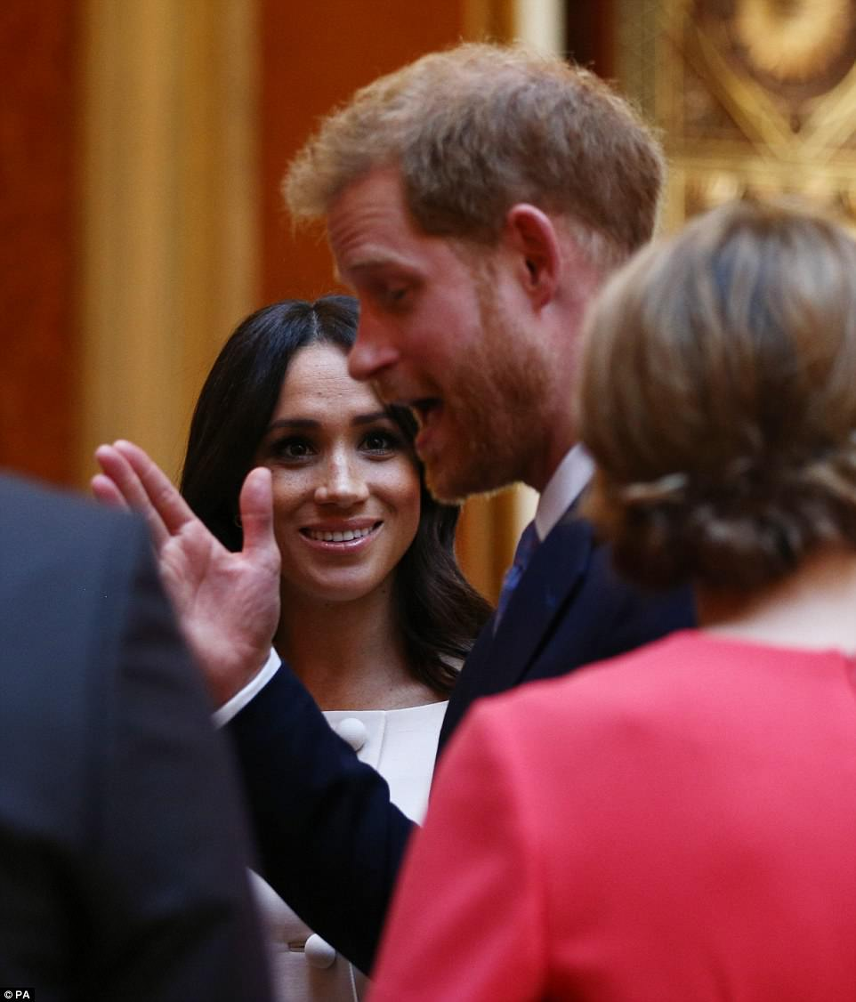 Smitten: Prince Harry looked animated as he chatted to those at the event as a smiling Meghan listened in
