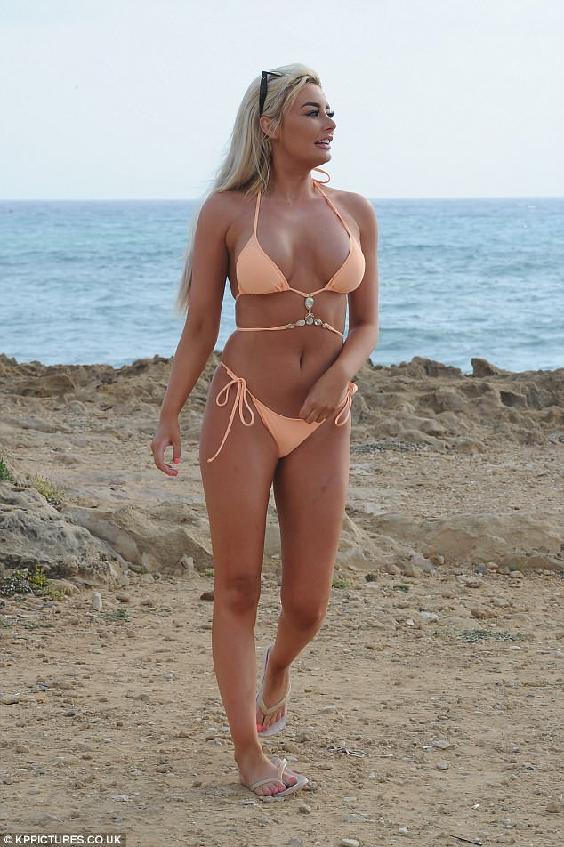 Chest a glimpse: Showcasing her ample chest, the blonde bombshell donned a peach strappy bikini top that featured a dazzling array of gems artfully placed beneath her cleavage