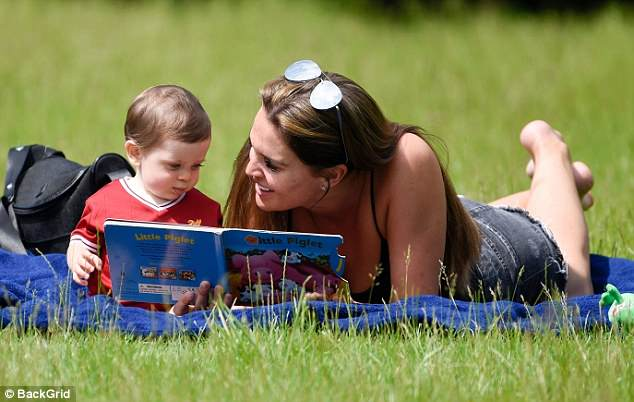 Smiles for miles:Danielle slipped off her shoes as she laid out on a blue towel to enjoy the sunshine with her tot after confirming plans to undergo gender selection for her fifth child