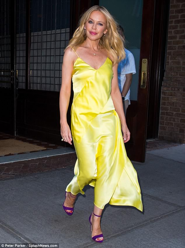 Stunning:Kylie Minogue, 50, looked radiant in a striking yellow silk slip dress in New York on Monday after admitting life in her 50s is 'better than ever'