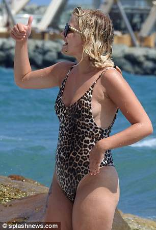 Wild thing: The actress, 22, turned heads in a stylish leopard print swimsuit as she and her beau frolicked in the sea