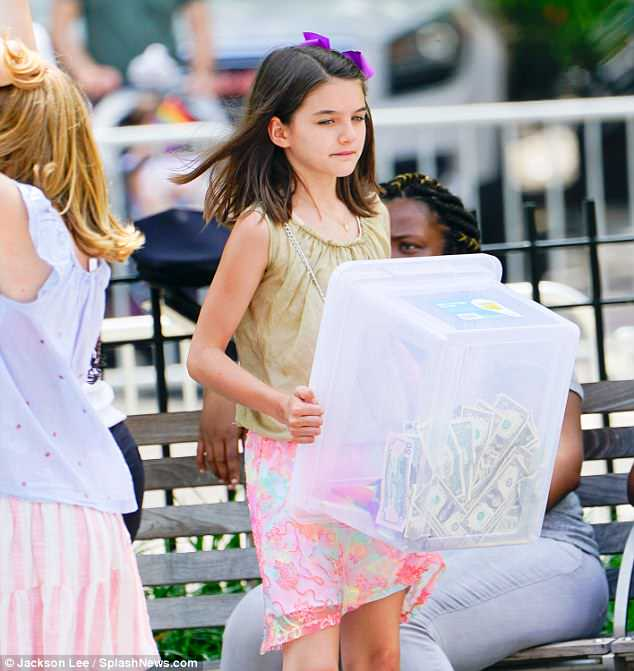 The look: The child had on a greenish tank top with a pink skirt and a star spangled purse worn crossbody style. She also carried a box full of cash