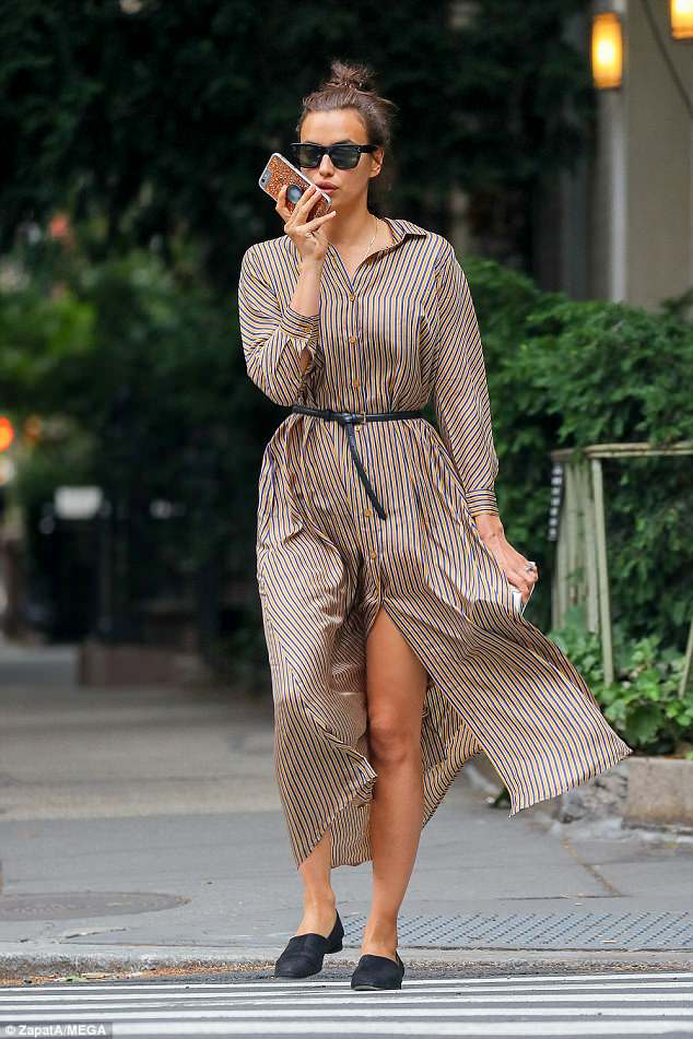 Earning her fashion stripes: Irina Shayk flashed her supermodel legs ina buttoned up shirt dress as she enjoyed a stroll in New York on Saturday