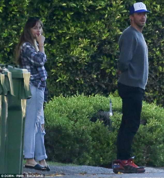 Intimate stroll: Dakota Johnson and Chris Martin were spotted in a rare moment of PDA while walking the starlet's dog around Malibu together on Sunday