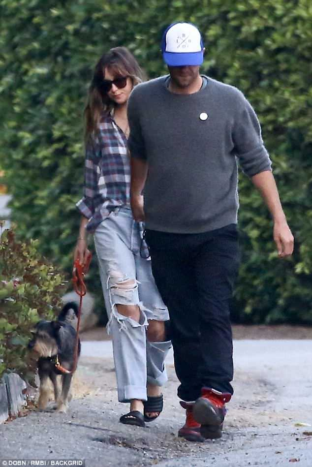 Easy going: The Fifty Shades actress dressed down in a blue plaid top with distressed denim cuffed at the bottom