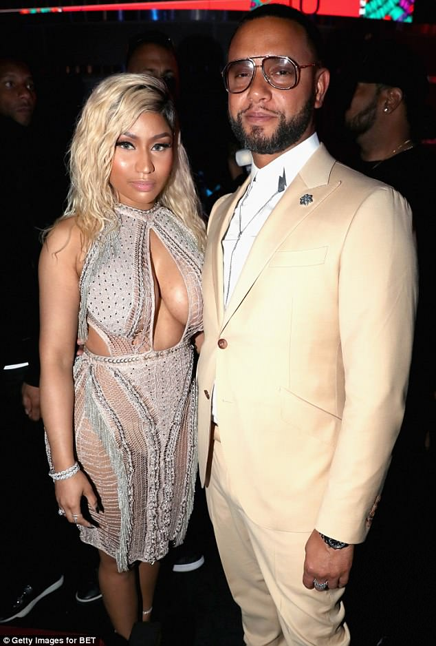 Flawless: The 35-year-old rapper chose a silver and white cut-out mini, which had a mesh skirt that put her nude underwear on display; pictured with Director X