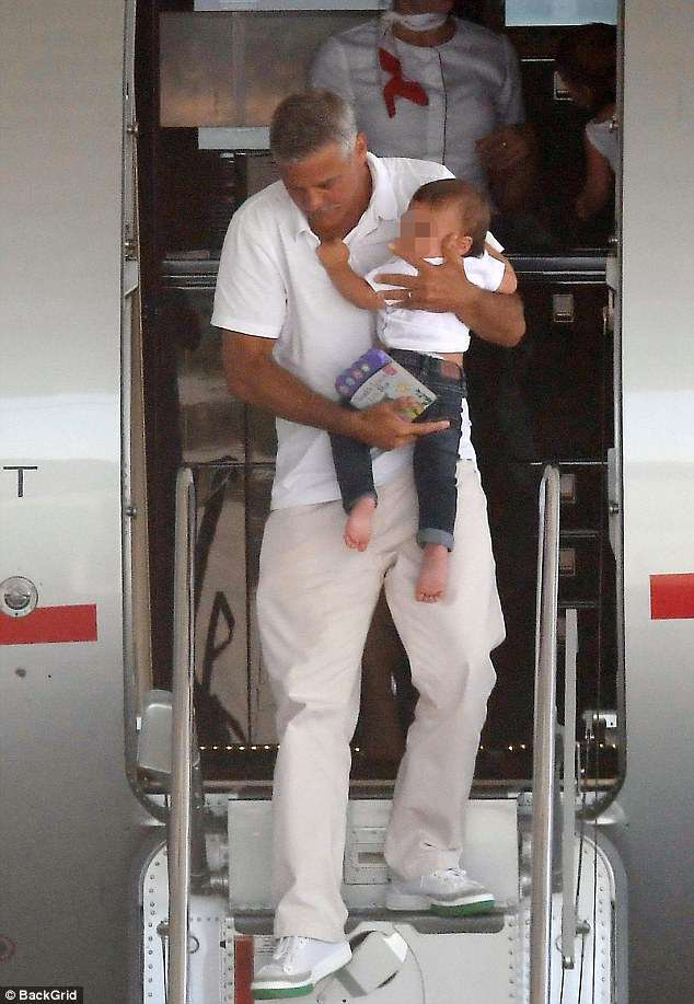 Handsome papa:Clooney was fashionable in a white shirt with light khaki slacks and thick-soled white sneakers. He also wore his grey hair very short and seemed to have a deep Mediterranean tan