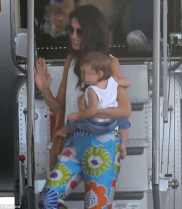 With her little girl:She was likely holding onto Ella who was dressed in a white tank top and blue leggings