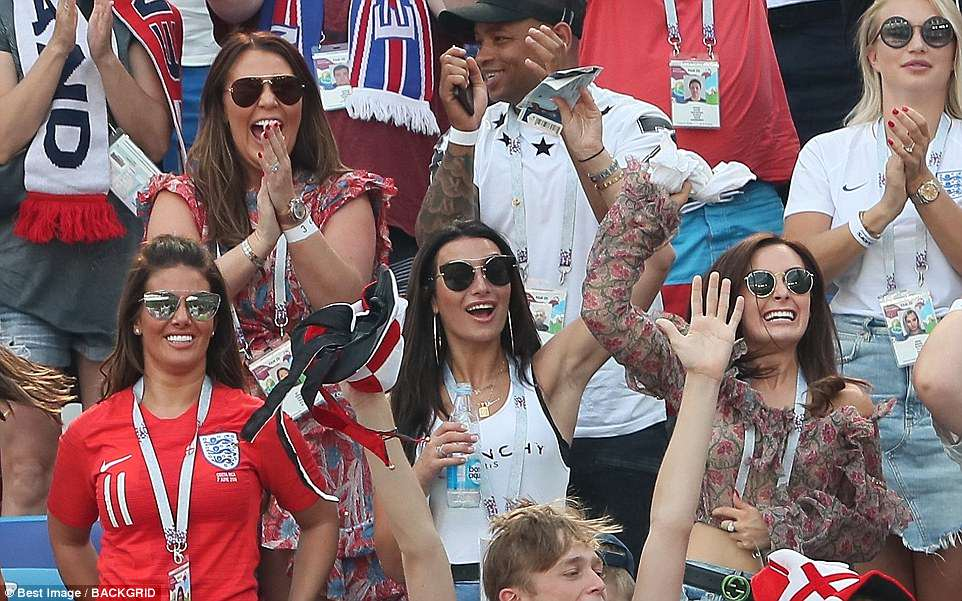 Rebekah Vardy (far left) could be seen flashing a wide smile as she cheered on her husband from the stands, along with fellow WAGs including Annie Kilner (centre) and Millie Savage (far right)