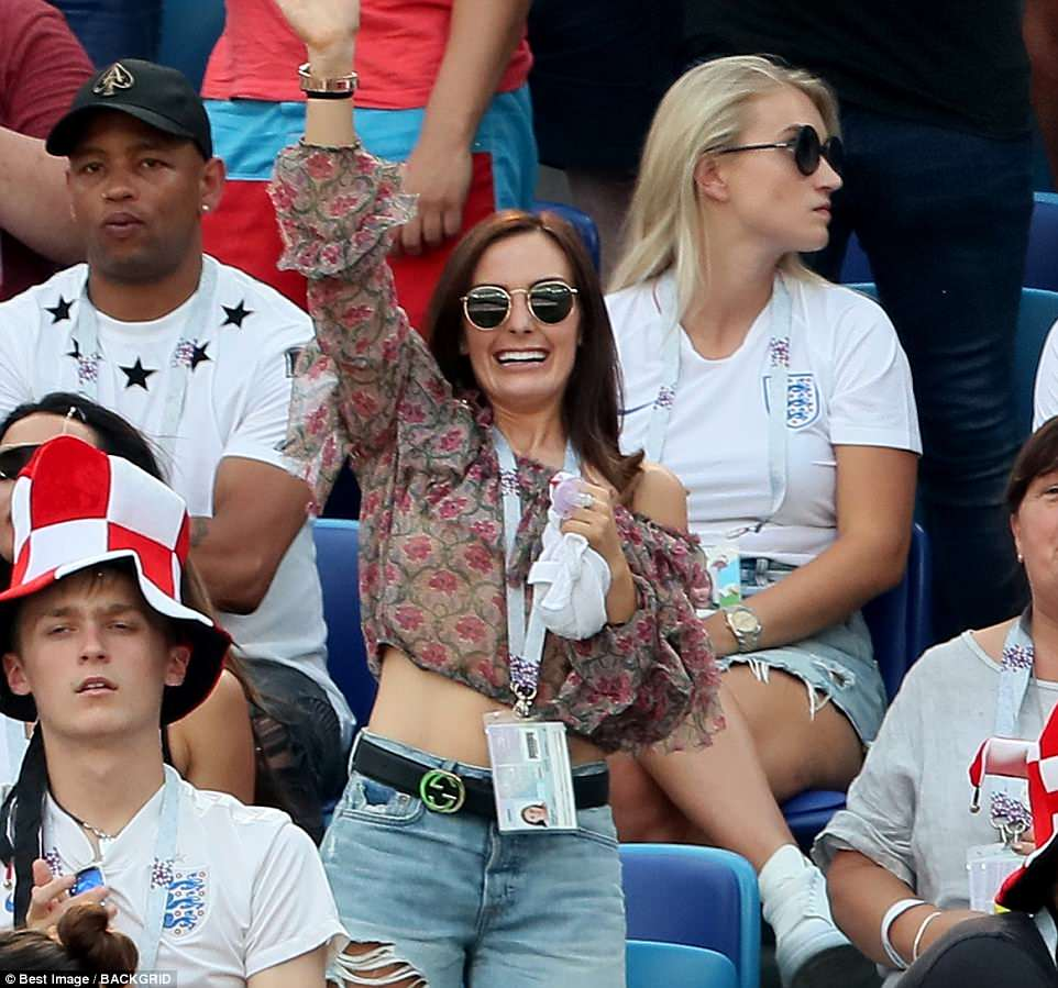 John Stones' partner Millie, who opted for a floral crop top and shorts, looked delighted during the game