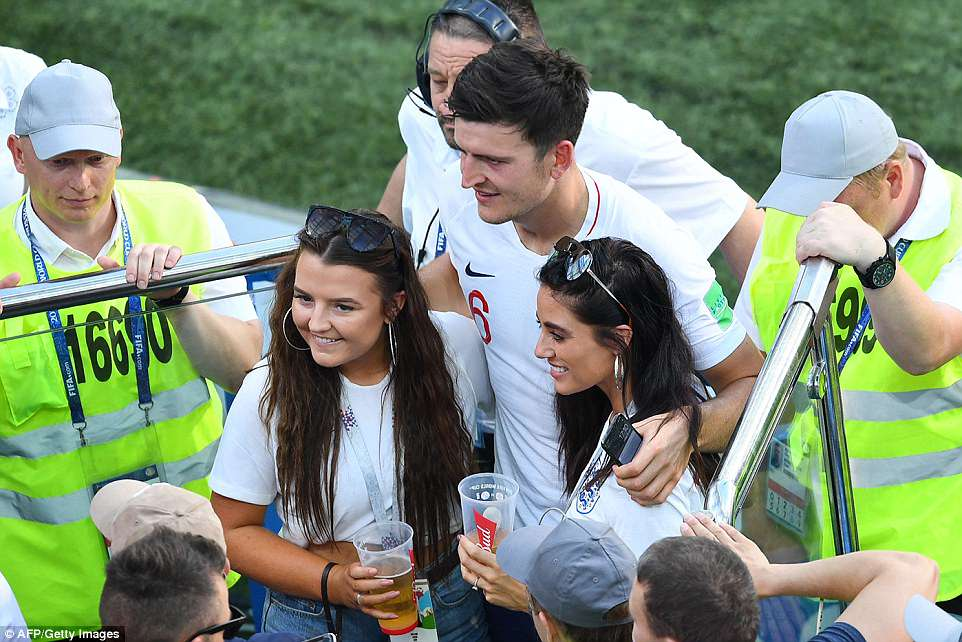 Fern (right) later went down to pose for pictures with her boyfriend Harry Maguire (centre) following the match