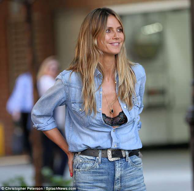 Chambray champ: The faded denim top was tucked into her equally faded and ripped denim pants as a bejeweled belt fir snugly around her lithe waist