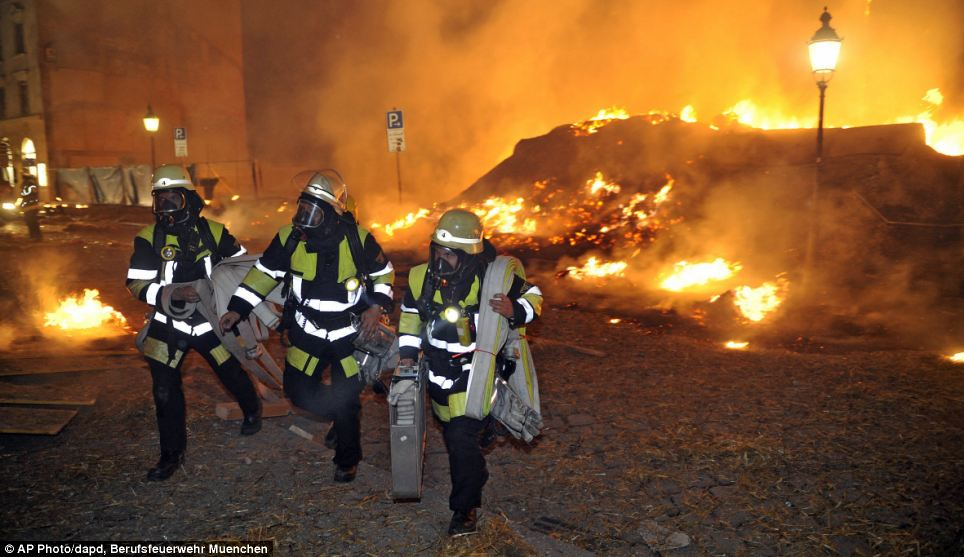 Inferno: Munich firefighters work to tackle fires caused by the bomb detonation. Bales of hay used to cushion the blast were set alight and blown across the area