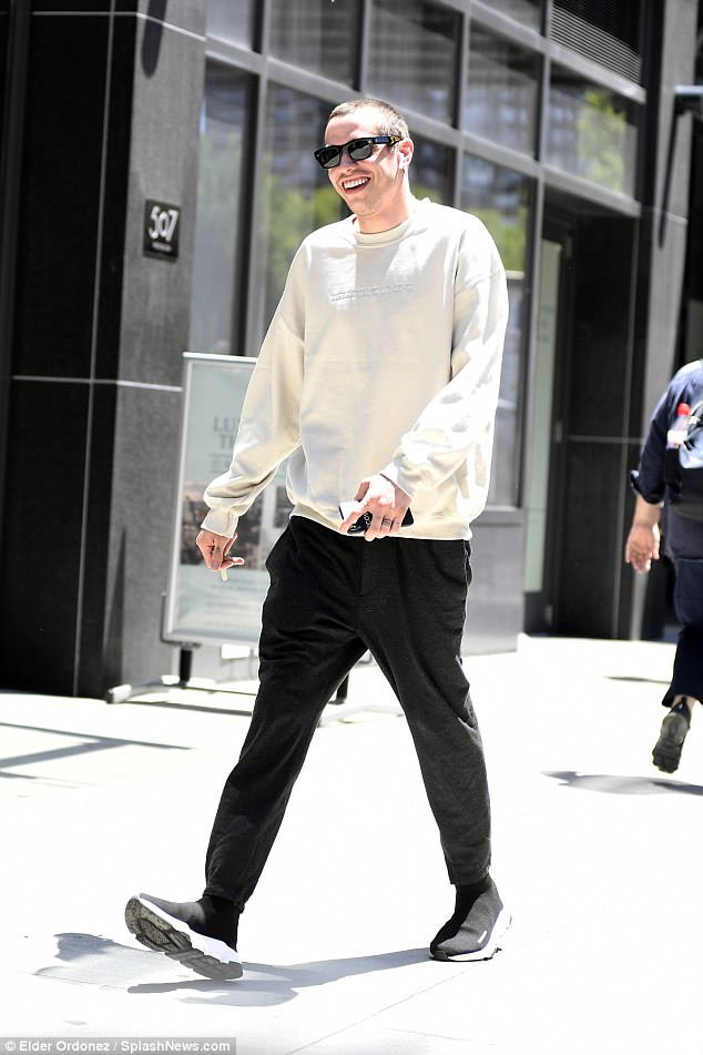 All smiles: Davidson was dressed in a white sweatshirt and black sweat pants as he took a solo walk through New York on Tuesday
