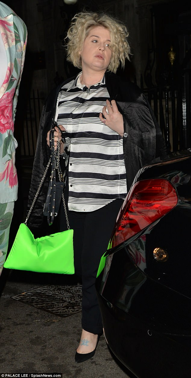 Joining her: Meanwhile Kelly opted for a stripped button down top and chic black trousers