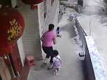 A little girl is pushing her younger sister in a stroller outside her home in China