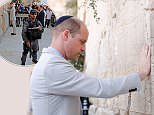 With a yarmulke on his head, William placed a written prayer on a folded piece of paper into one of the cracks in Western Wall